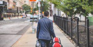 Homme marchant de dos avec une valise